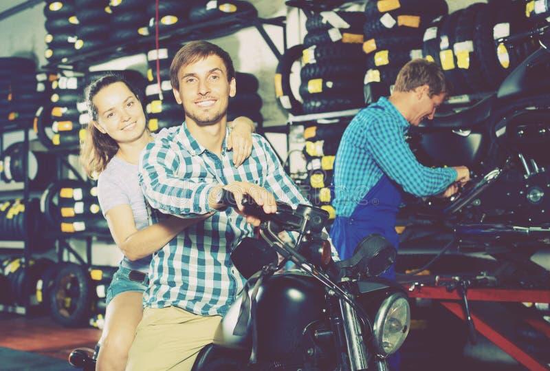 Жизнерадостные пары сидя на мотоцикле на сервисный центр стоковые изображения rf