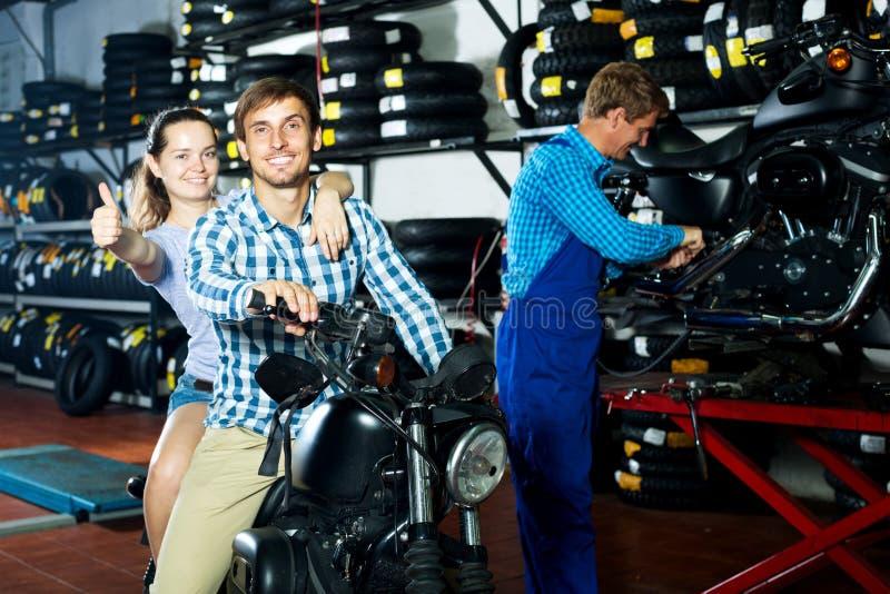 Жизнерадостные пары сидя на мотоцикле на сервисный центр стоковые фотографии rf