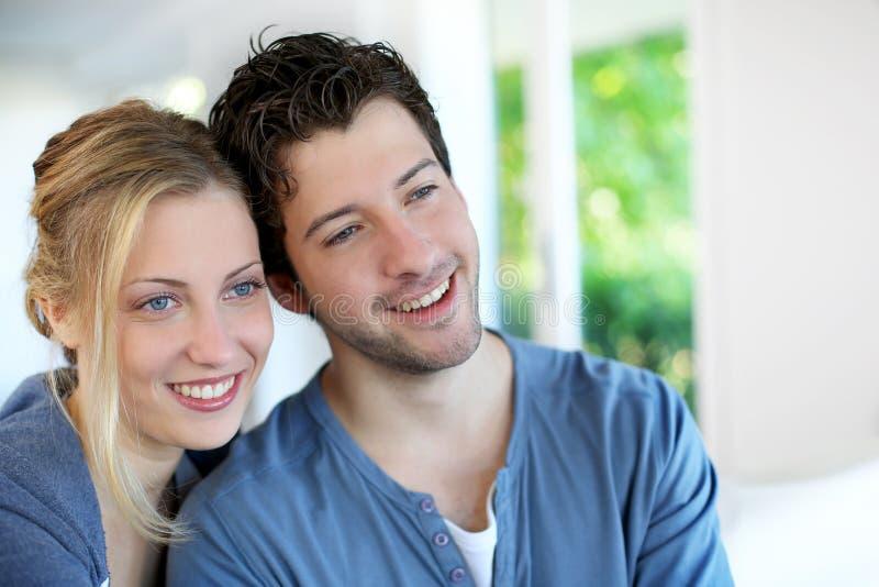 Жизнерадостные пары сидя на софе дома стоковая фотография rf
