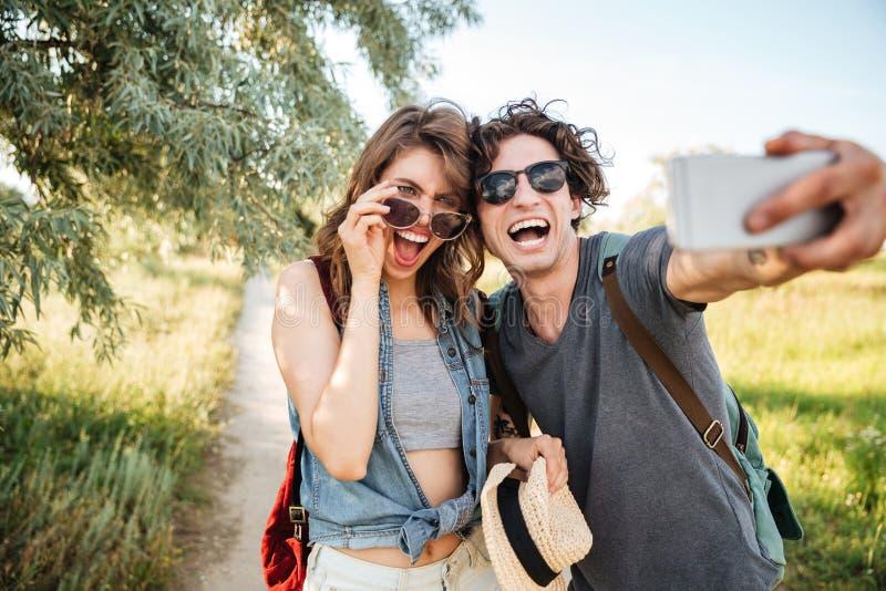 Жизнерадостные пары w в лесе и делая selfie стоковые изображения rf