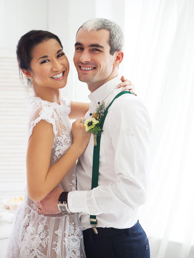 Жизнерадостные пожененные пары в белой комнате стоковые фото