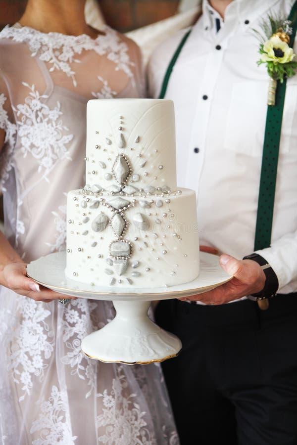 Жизнерадостные пожененные пары держа свадебный пирог стоковое фото
