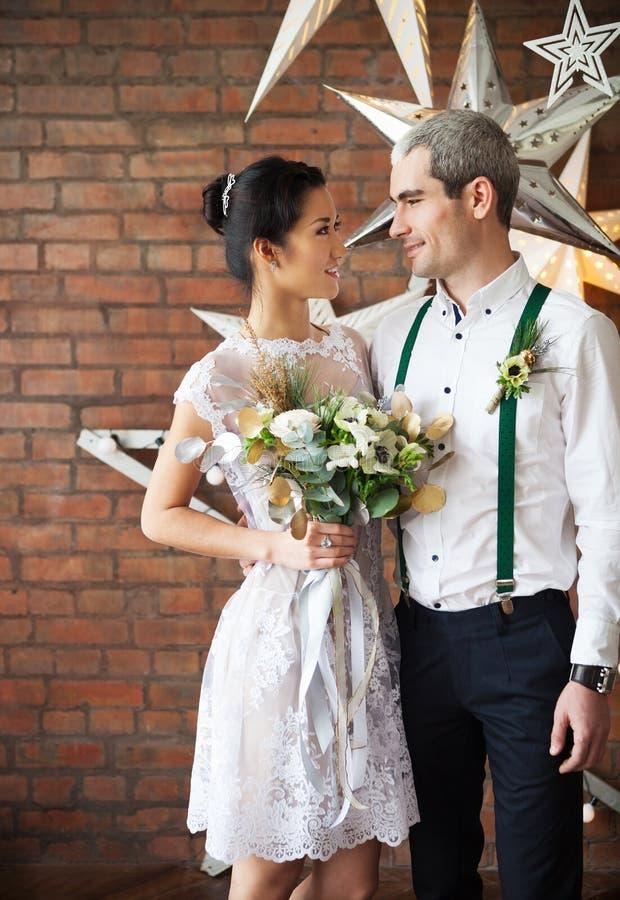 Жизнерадостные пожененные пары около кирпичной стены стоковые фотографии rf