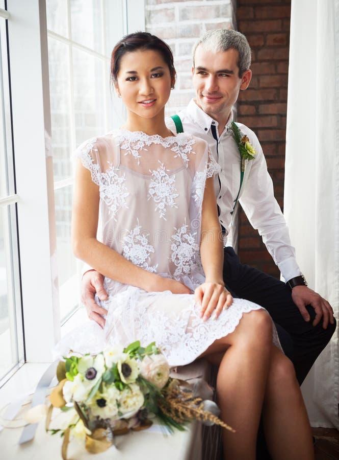 Жизнерадостные пожененные пары около окна стоковые изображения