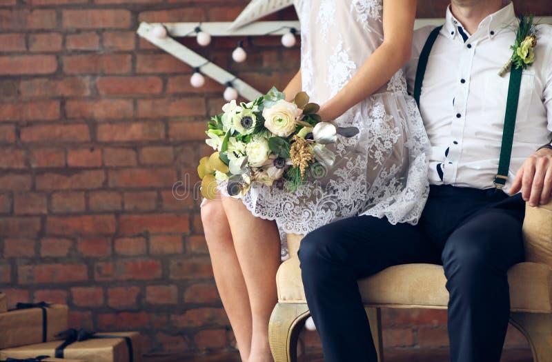 Жизнерадостные пожененные пары стоя около кирпичной стены стоковое изображение rf
