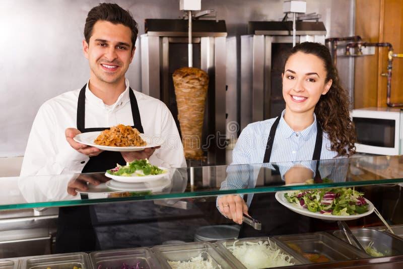 Жизнерадостные работники работая с kebab стоковые фотографии rf