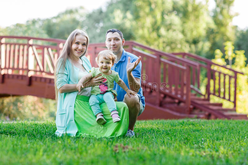 Жизнерадостные родители с маленькой дочерью рядом с мостом стоковая фотография