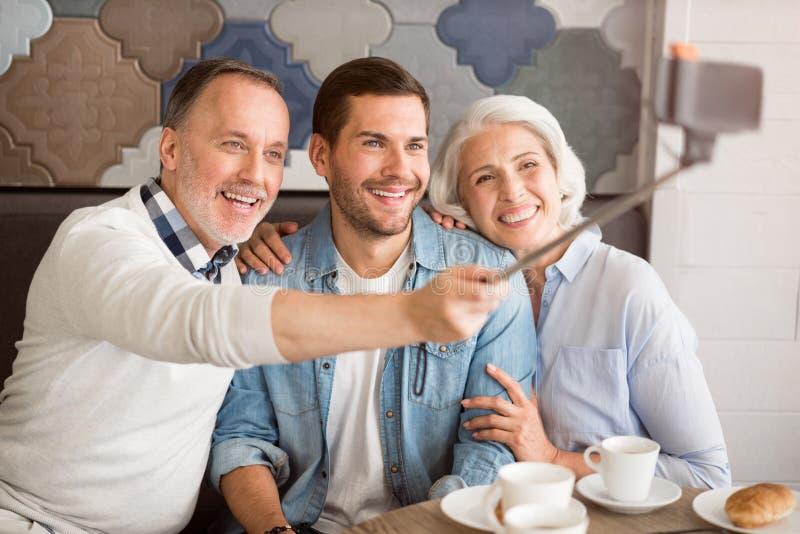 Жизнерадостные старшие пары отдыхая с их взрослым внуком стоковые изображения rf