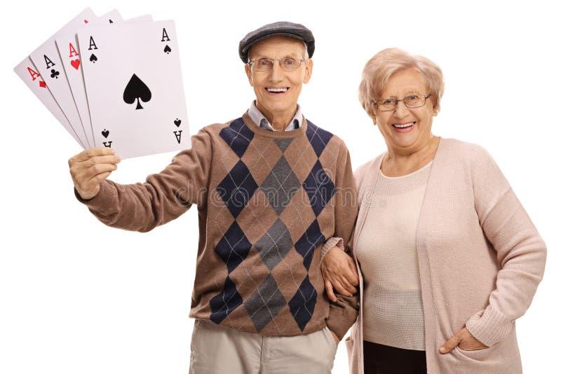 Жизнерадостные старшии с 4 карточками тузов играя стоковые изображения