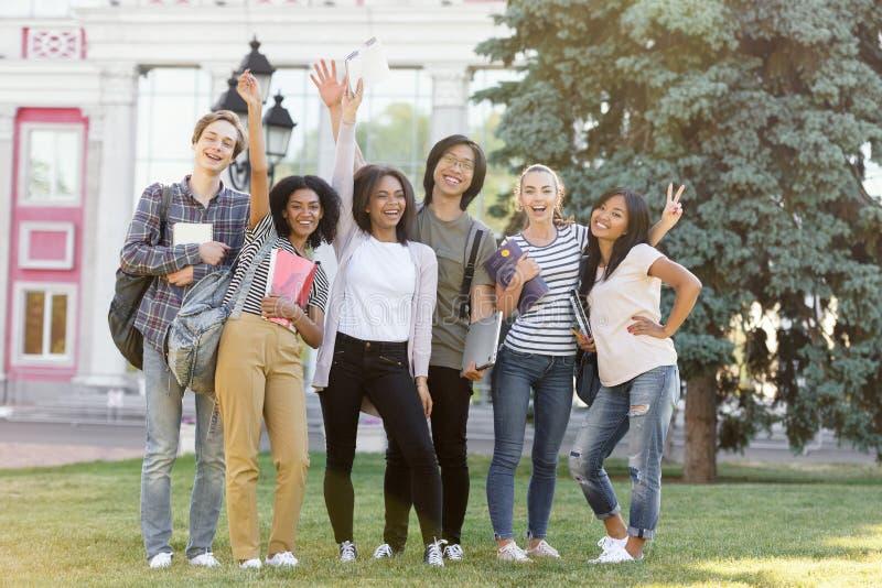 Жизнерадостные студенты стоя и развевая outdoors стоковые фотографии rf