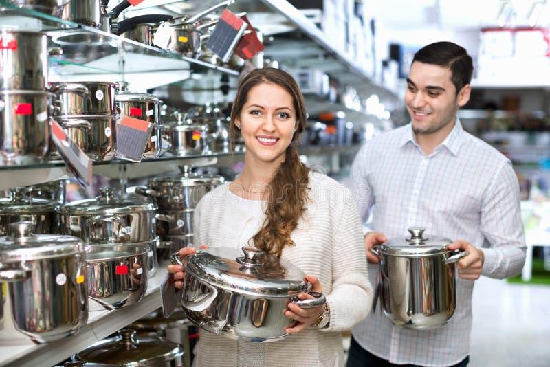 Жизнерадостные усмехаясь пары в разделе cookware стоковые изображения rf