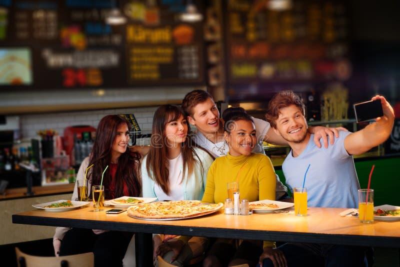 Жизнерадостные multiracial друзья имея потеху есть в пиццерии стоковые фото