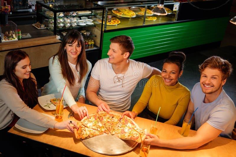 Жизнерадостные multiracial друзья имея потеху есть в пиццерии стоковое изображение rf
