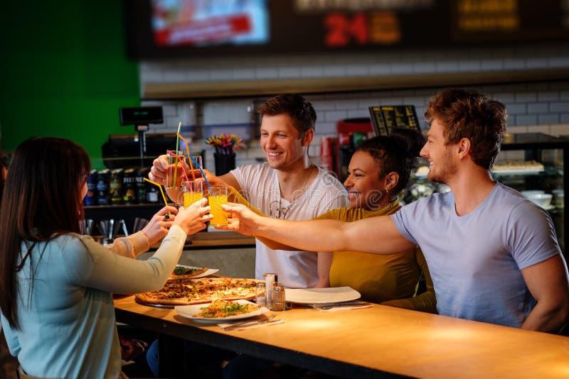Жизнерадостные multiracial друзья имея потеху есть в пиццерии стоковое фото rf