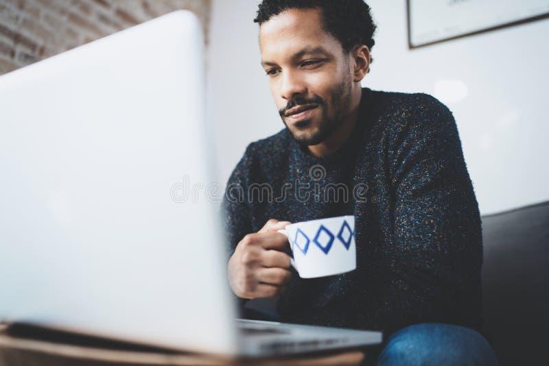 Жизнерадостный африканский человек используя компьютер и усмехающся пока сидящ на софе Черный парень держа керамическую чашку в р стоковые изображения