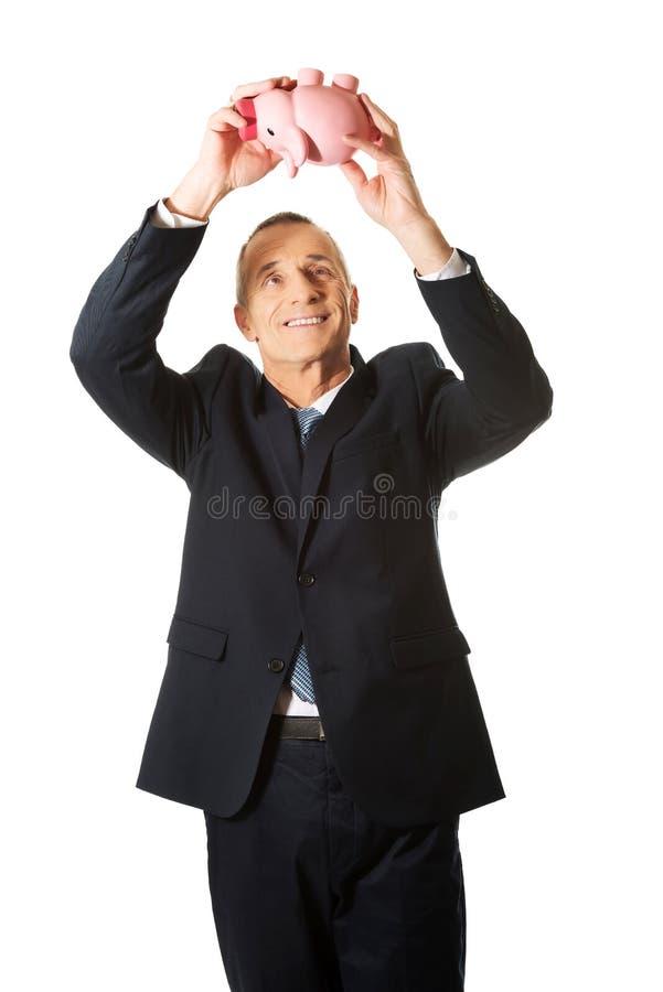 Жизнерадостный бизнесмен держа piggybank стоковое изображение rf