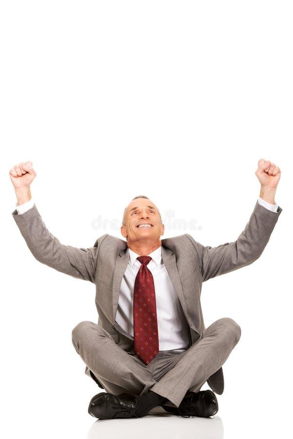 Жизнерадостный бизнесмен сидя положив ногу на ногу стоковые изображения rf