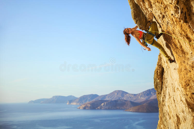 Жизнерадостный женский альпинист на трудной трассе стоковое изображение