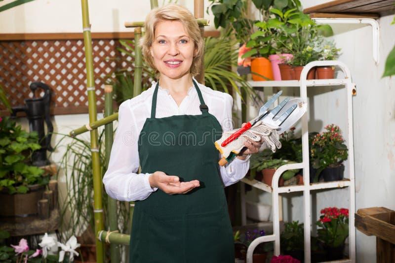 Жизнерадостный женский флорист стоя среди заводов стоковая фотография