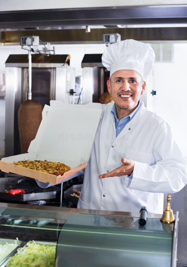 Жизнерадостный зрелый кашевар человека давая свеже сделанную пиццу стоковая фотография