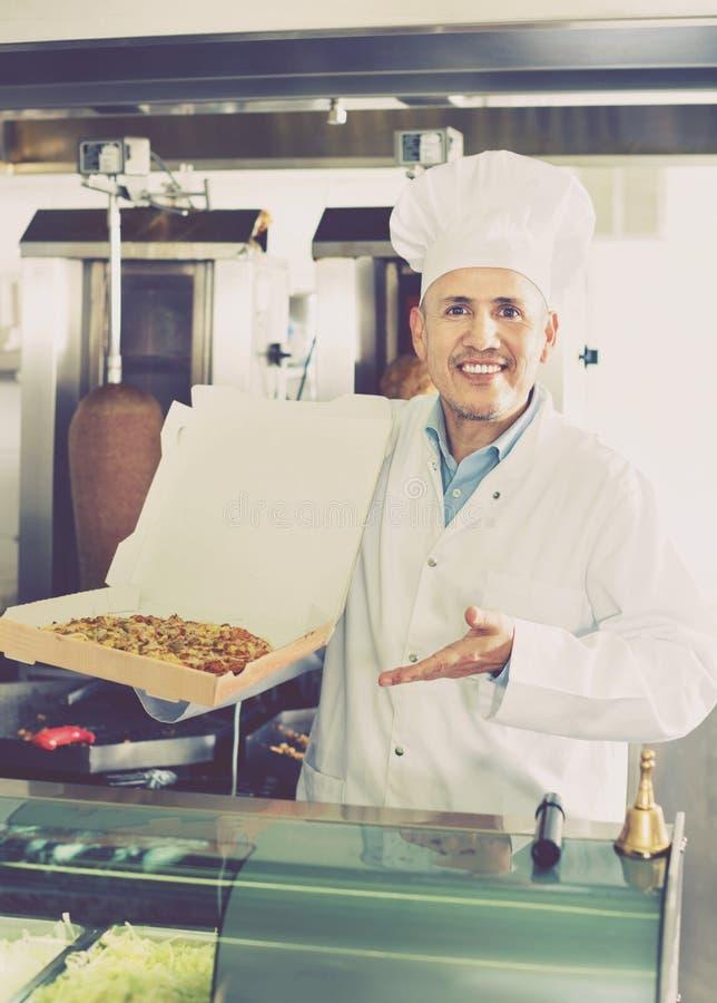Жизнерадостный зрелый кашевар человека давая свеже сделанную пиццу стоковые изображения rf