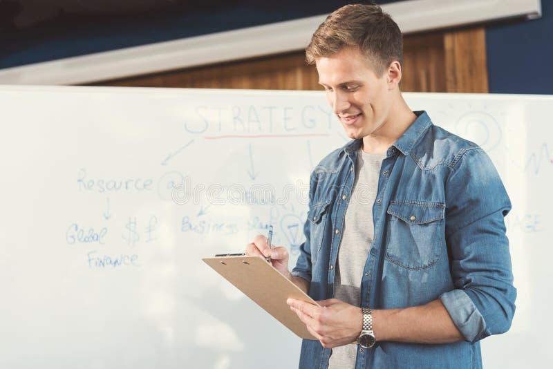 Жизнерадостный моложавый парень изучая на работе в комнате офиса стоковая фотография rf