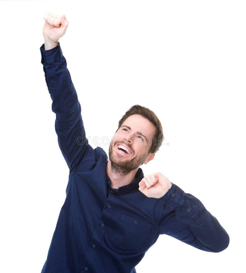 Жизнерадостный молодой человек празднуя при поднятые оружия стоковые фотографии rf