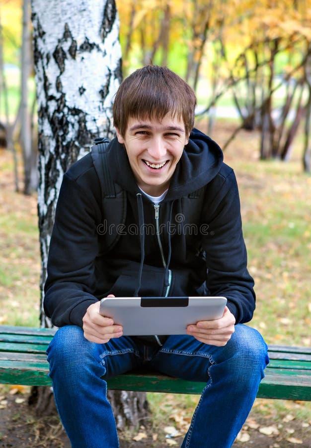 Жизнерадостный молодой человек с таблеткой стоковые фото