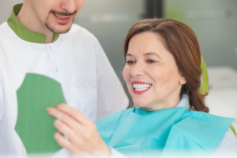Жизнерадостный мужской ортодонт работает с пациентом стоковые изображения rf