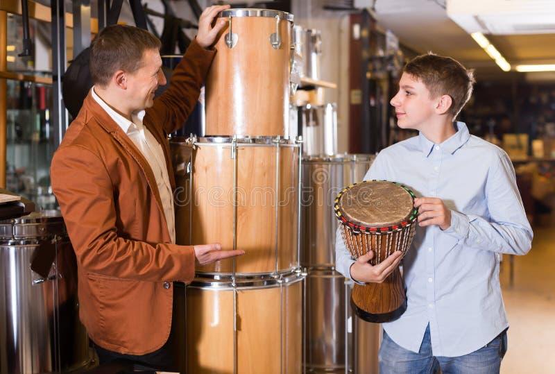 Жизнерадостный отец и сын рассматривая этнические барабанчики стоковое изображение