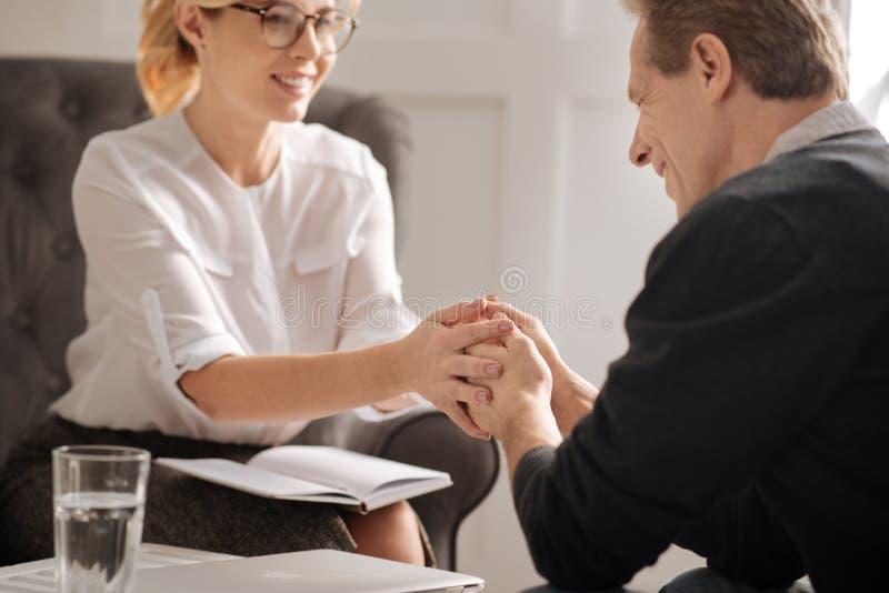 Жизнерадостный положительный терапевт держа руки ее пациента стоковые фото