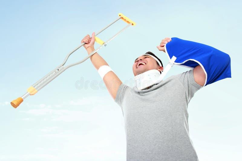 Жизнерадостный раненый молодой человек задерживает костыль стоковая фотография