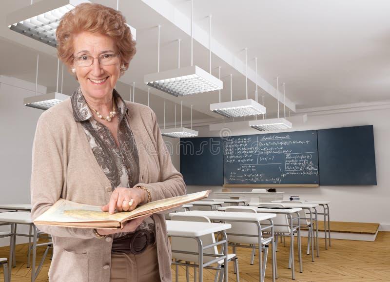 Жизнерадостный старший учитель указывая к книге стоковые изображения rf