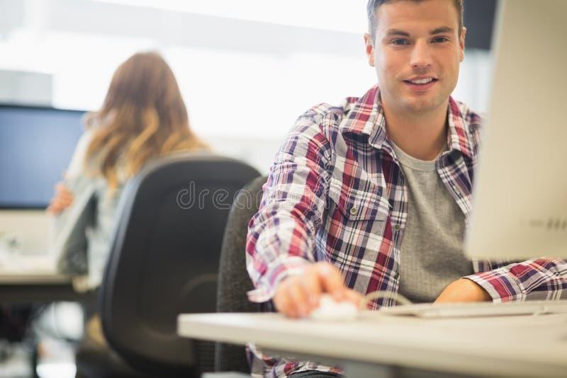 Жизнерадостный студент смотря камеру в компьютерной комнате стоковая фотография rf
