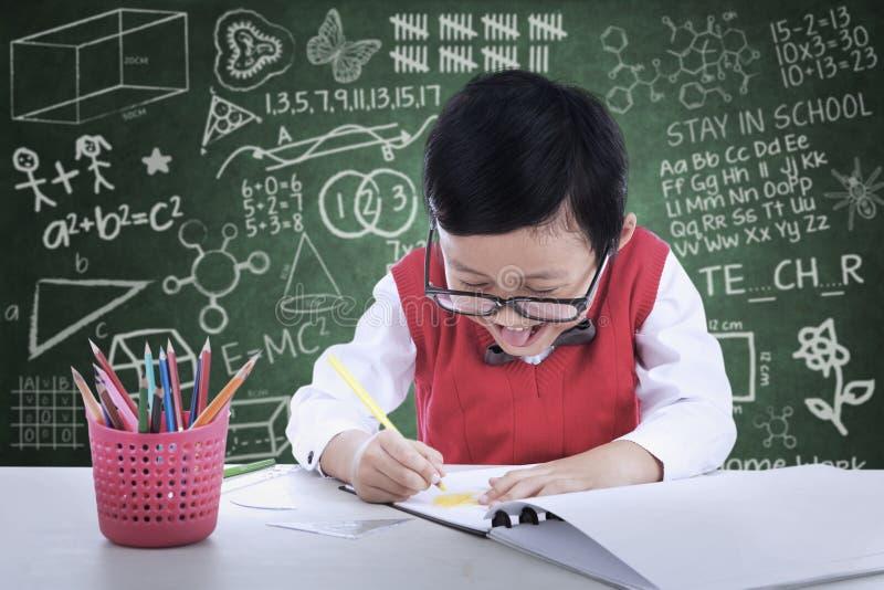 Жизнерадостный чертеж мальчика в классе стоковые изображения rf