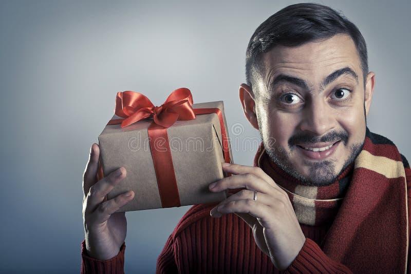 Жизнерадостный человек тряся подарочную коробку и усмехаться стоковые изображения