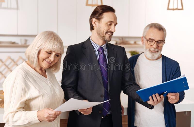 Жизнерадостный юрист демонстрируя контракт для пожилых пар клиентов стоковая фотография rf