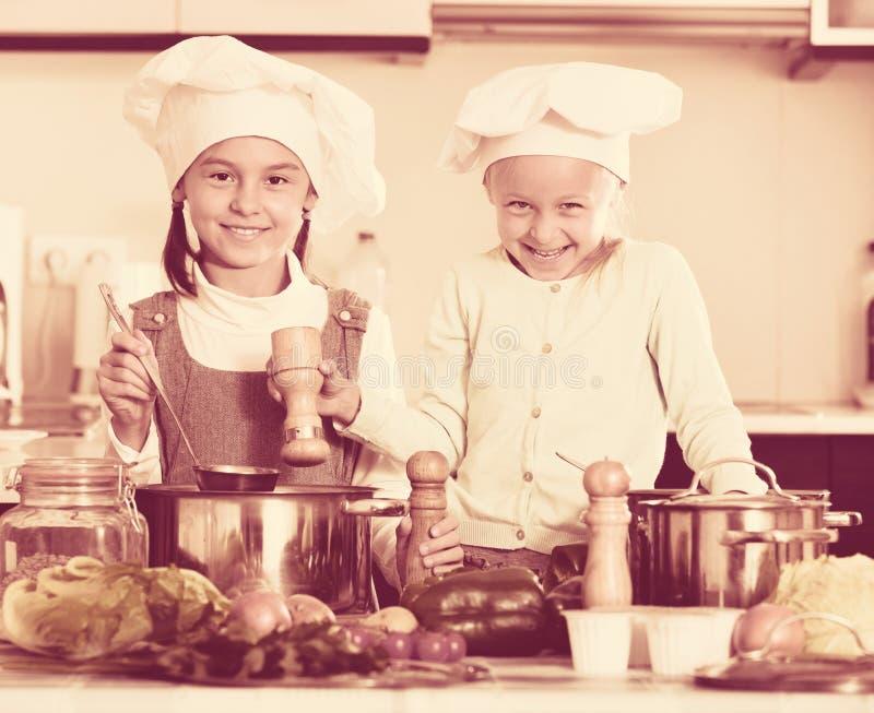 2 жизнерадостных счастливых девушки варя овощной суп стоковая фотография