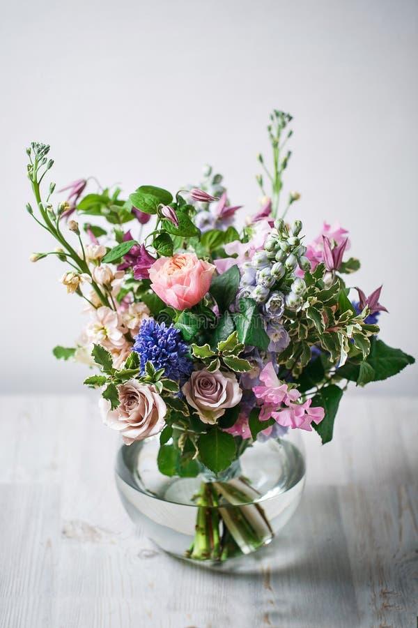 1 жизнь все еще деревянная античная таблица, стеклянная ваза с смешанным букетом красивейшие цветки стоковые изображения rf