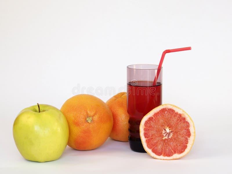 1 жизнь все еще На белой предпосылке являются следующими: яблоко, 2 всех грейпфрута и стекло сока, от которого вставляет вне труб стоковое фото rf