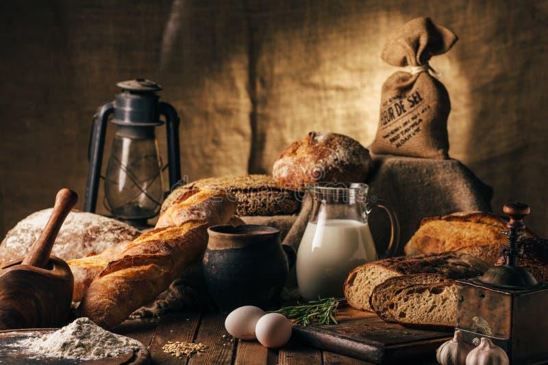 1 жизнь все еще Сельскохозяйственные продукты: яичка, молоко, свежий хлеб на деревянном столе Конец-вверх один фокус стоковые фото