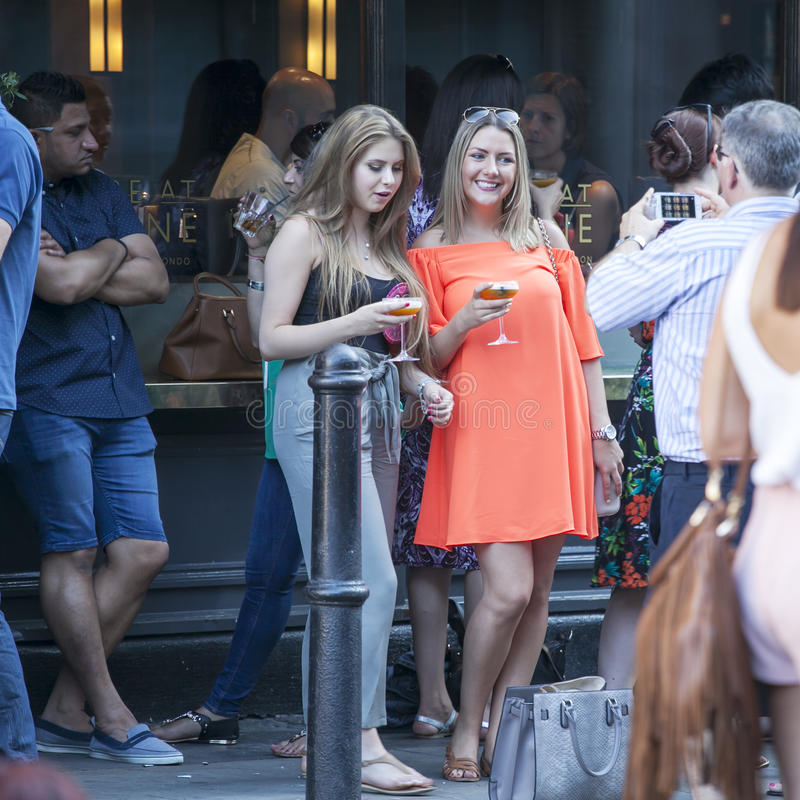 Жизнь кафа улицы Курчавая усмехаясь девушка разговаривая с друзьями вне бара стоковая фотография