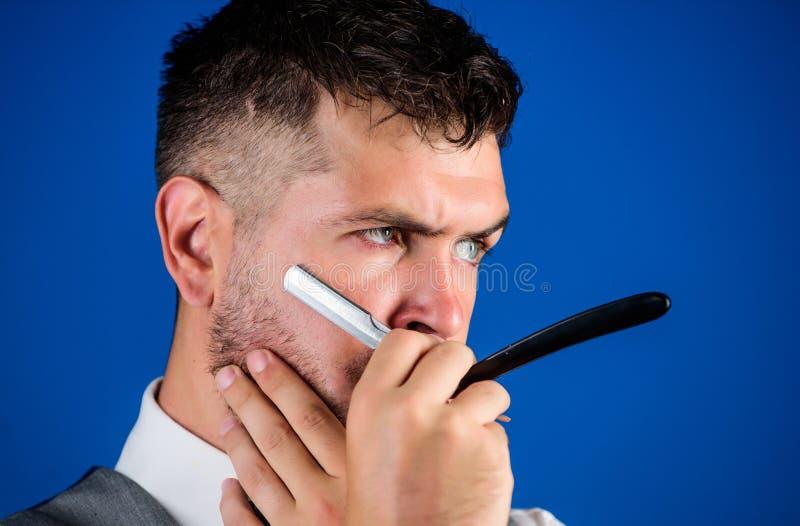 Жилет человека с предпосылкой прямой бритвы владением бабочки голубой Концепция искусства парикмахера Хипстер парикмахера небриты стоковое изображение