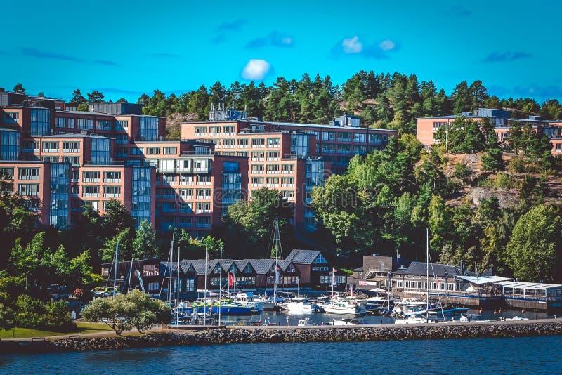 Жилые дома расположены в лесе рядом с доком для шлюпок и кораблей на солнечный день, острова Швеции стоковые фото