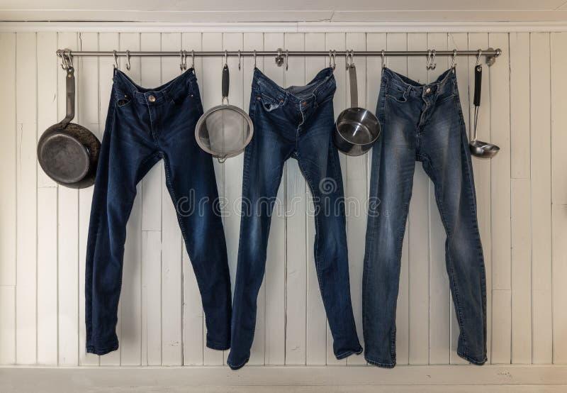 3 джинса вися на рельсе кухни для того чтобы высушить стоковое изображение rf