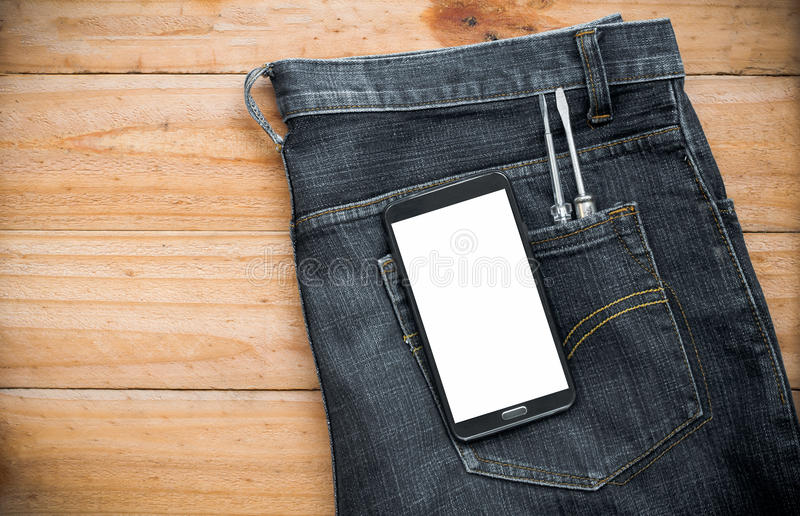 джинсы с инструментом мобильного телефона и отвертки в карманн на wo стоковое изображение rf