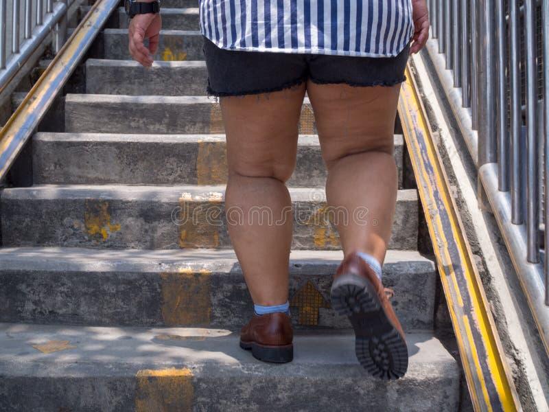 Жирная нога женщины, который нужно шагнуть вверх по лестницам стоковое фото