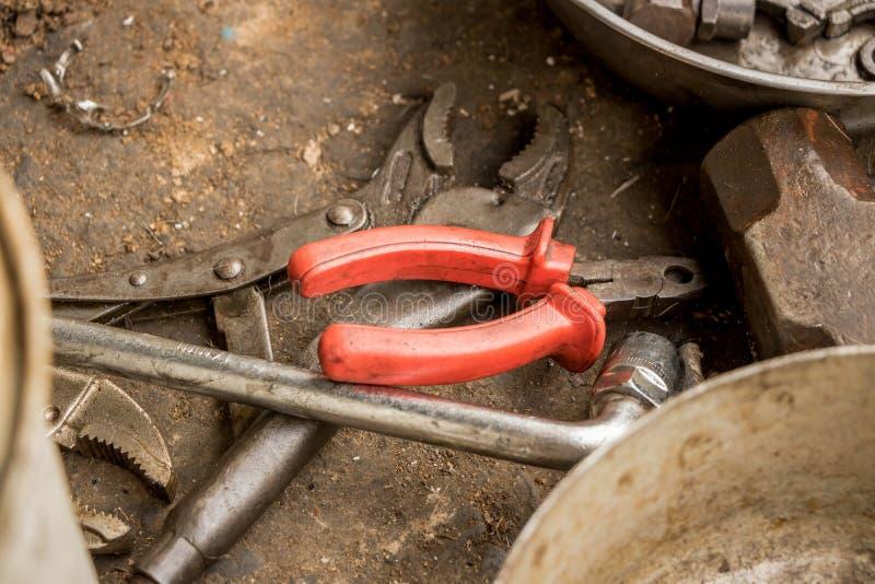 Жирные старые плоскогубцы с гаечным ключом резца провода и регулируемого ключа на грязной земле стоковая фотография