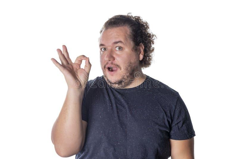 Жирный смешной человек показывает знак ок, демонстрирует что все отлично, жесты против белой стены стоковые изображения rf