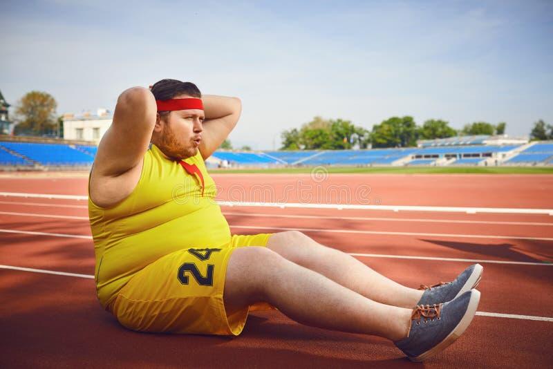 Жирный человек делая подбрюшные тренировки в стадионе стоковое фото rf